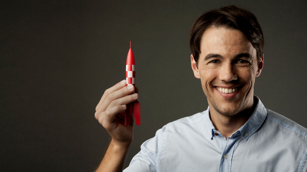 Matthew Pollard holding a small red and white rocket